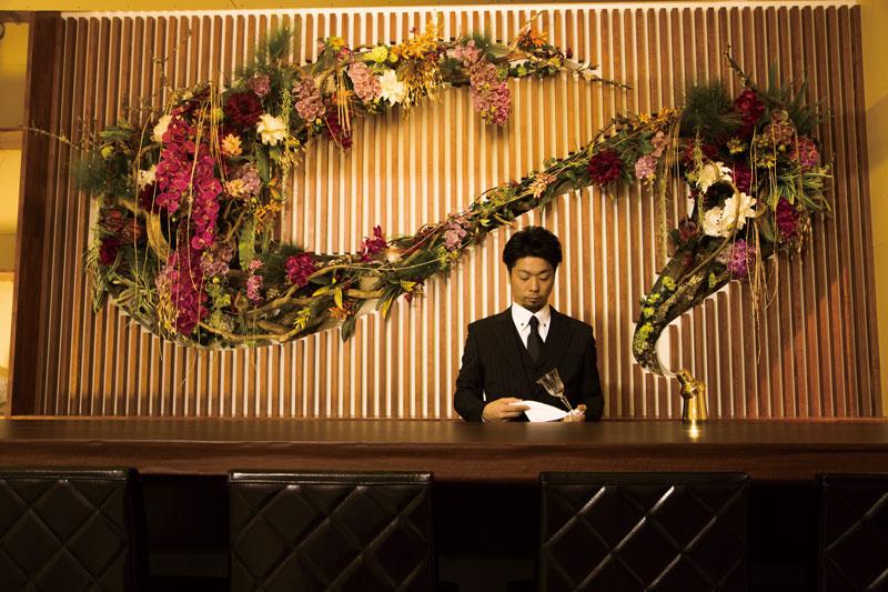 中村有孝氏の長崎くんちの龍踊りをモチーフとした作品「DANCE」を背にカウンタ-に立つオーナー・西岡さん