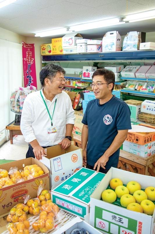 創業100年を超える〈古川青果〉の店主とともに。上田さん曰く「あの人は釣りの達人」とのこと。地域の頼れる存在だ